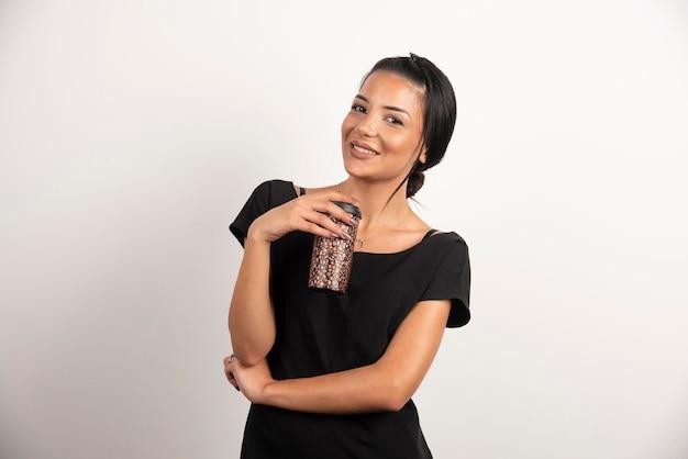 Brunetka kobieta z filiżanką kawy śmiejąc się na białej ścianie.