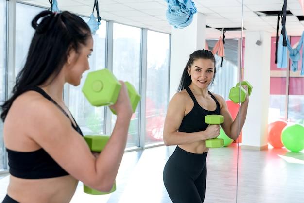 Brunetka kobieta z hantlami, trening w siłowni