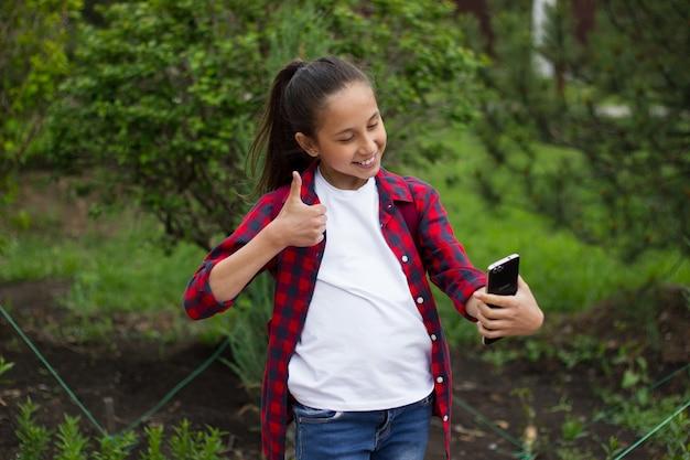Brunetka komunikuje się przez telefon w komunikatorze robi sobie selfie i pokazuje fajnie