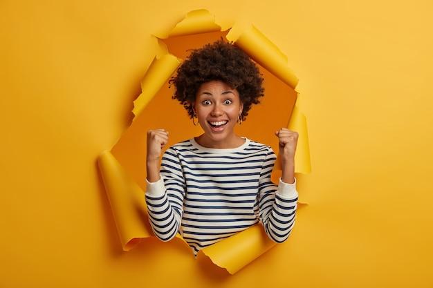 Brunetka, kręcona dorosła kobieta w swobodnym swetrze w paski wykonuje gest zwycięstwa po osiągnięciu celu, raduje się z sukcesu, uśmiecha się szeroko, pozuje w żółtej podartej papierowej dziurze
