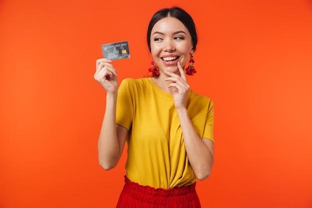 Brunetka latynoska 20-latka ubrana w spódnicę uśmiechnięta i trzymająca kartę kredytową odizolowaną od czerwonej ściany
