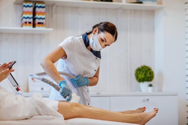 Brunetka lekarz w niebieskich rękawiczkach medycznych i masce trzyma maszynę do depilacji i używa jej na nogach kobiety.