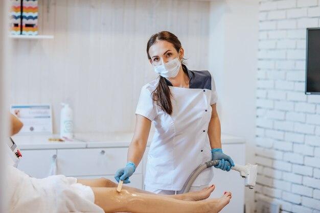 Brunetka lekarz w rękawiczkach medycznych i masce za pomocą maszyny do depilacji na nogach kobiety