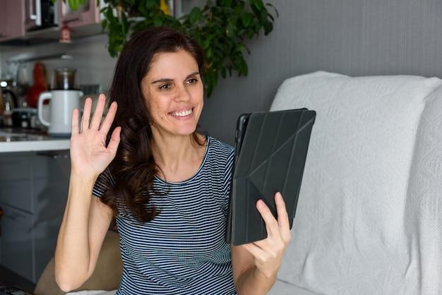Brunetka macha ręką, wita się i spogląda na tablet w swoim mieszkaniu. zabawne powitanie online. używać komputera. edukacja i praca online na odległość