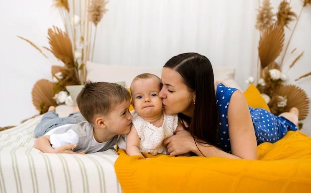Brunetka mama i syn całują swoją córeczkę na łóżku w pokoju