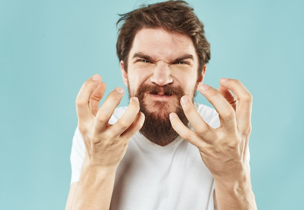 Brunetka mężczyzna gestykuluje rękami na niebieskim tle emocje modelu drażliwość