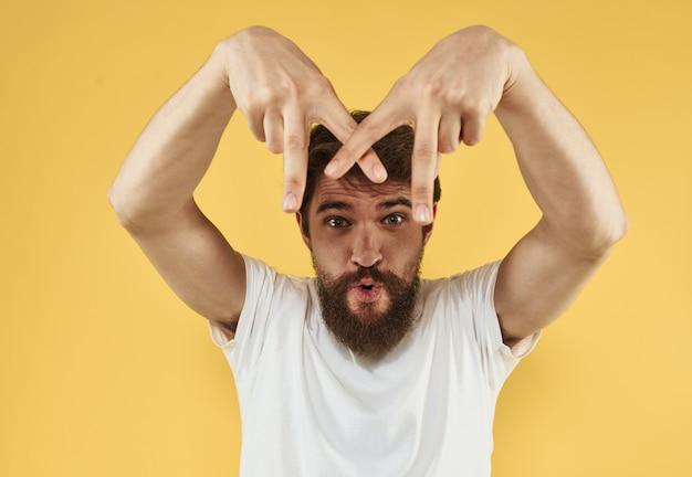 Brunetka mężczyzna gestykuluje rękami na żółtym tle przycięty widok. wysokiej jakości zdjęcie