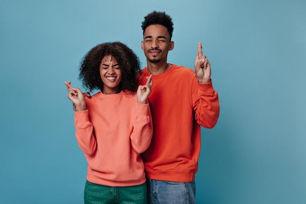 Brunetka mężczyzna i kobieta krzyżują palce na niebieskiej ścianie