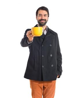 Brunetka mężczyzna trzyma filiżankę kawy