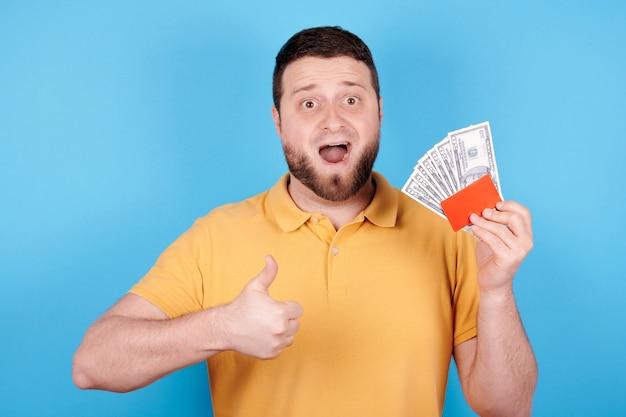 Brunetka mężczyzna trzyma w ręku czerwoną kartę kredytową i papierowe pieniądze, zaskoczona emocja. pojedynczo na niebieskim tle.