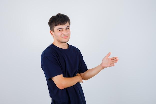 Brunetka mężczyzna udaje, że pokazuje coś w koszulce i wygląda wesoło, widok z przodu.