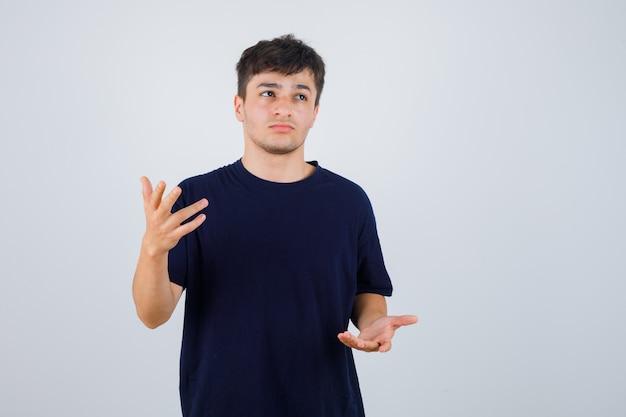 Brunetka mężczyzna udaje, że pokazuje coś w koszulce i wygląda zamyślony. przedni widok.