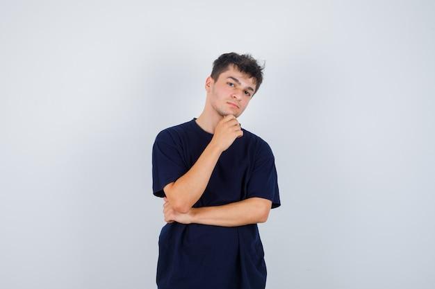 Brunetka mężczyzna w ciemny t-shirt, trzymając rękę na brodzie i patrząc tęsknie, widok z przodu.