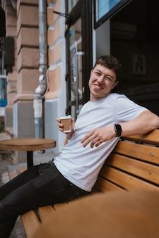 Brunetka mężczyzna w kawiarni ulicy pije kawę.
