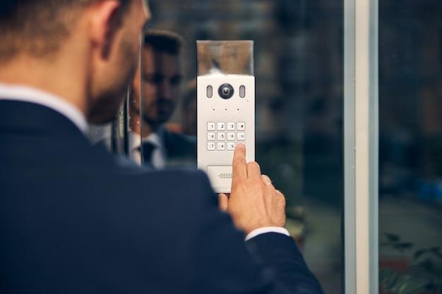 Brunetka mężczyzna w oficjalnym stroju stojący na zewnątrz, naciskając klawisz, aby otworzyć drzwi