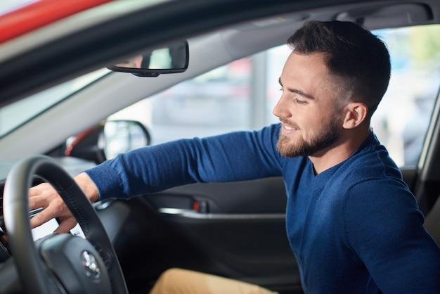 Brunetka mężczyzna z brodą w niebieskim swetrze, siedząc w nowym samochodzie.