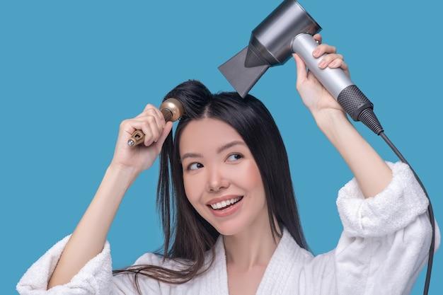 Brunetka młoda azjatycka kobieta suszy włosy i uśmiecha się
