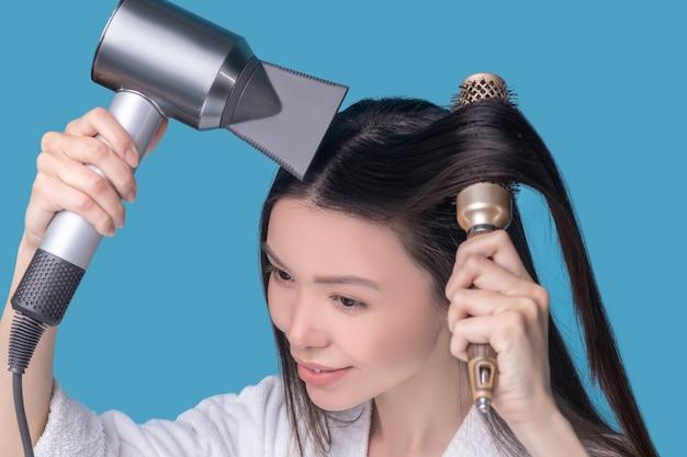 Brunetka młoda azjatycka kobieta suszy włosy