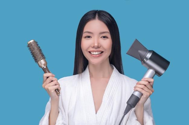 Brunetka młoda azjatykcia kobieta trzyma pędzel i suszarkę do włosów
