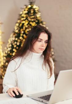 Brunetka młoda kobieta pracuje w domu zdalnie za laptopem iz dokumentami na tle choinki. świąteczna atmosfera i praca w domu. 2021