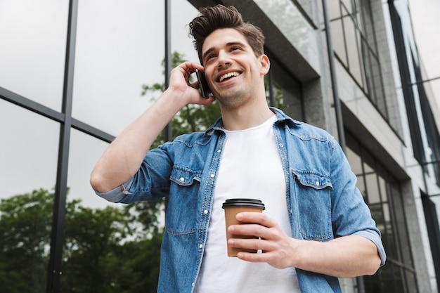 Brunetka młody mężczyzna w zwykłych ubraniach pije kawę na wynos i rozmawia przez telefon komórkowy, stojąc nad budynkiem