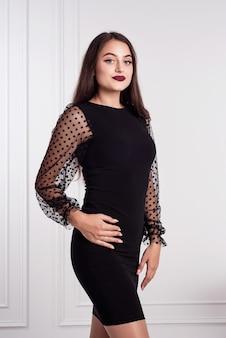 Brunetka model dziewczyna w czarnej krótkiej sukience. z długimi rękawami z gipiury