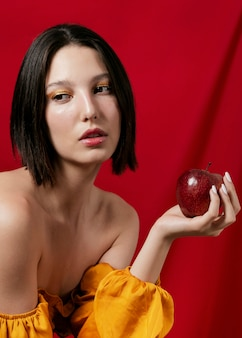Brunetka model pozuje z jabłkiem