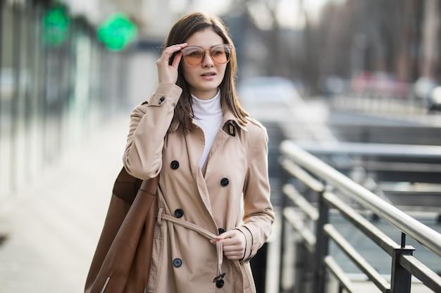 Brunetka model w przezroczystych okularach przeciwsłonecznych wychodzi na zewnątrz w jesienny dzień