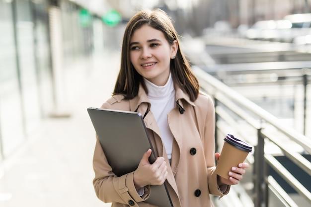 Brunetka model w przypadkowych ubraniach zostaje z laptopem i kawą na zewnątrz