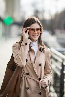 Brunetka model w transperent brown okularach przeciwsłonecznych chodzi wśrodku zakupy centrum handlowego w jesień dniu