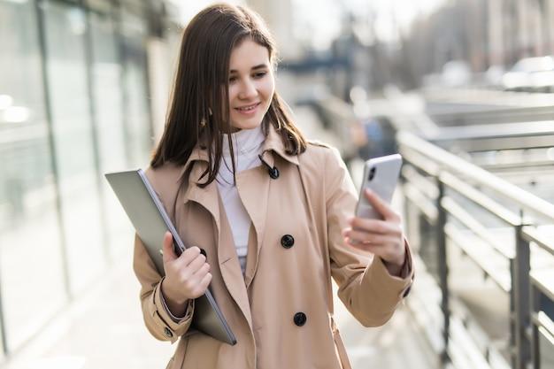 Brunetka model z laptopem w dłoniach ma połączenie wideo na swoim telefonie