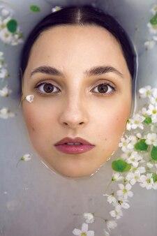 Brunetka modelka leży w białej kąpieli z mlekiem i małymi kwiatami