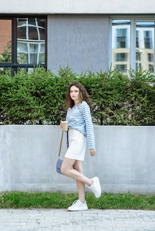 Brunetka modelka pozuje na zewnątrz w miejskim katalogu odzieży
