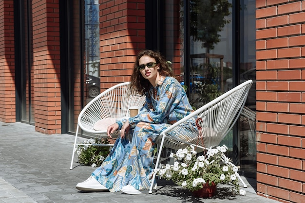 Brunetka modelka w okularach przeciwsłonecznych pozuje siedząc w nowej kolekcji letnich ubrań