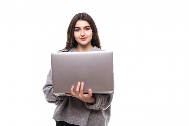 Brunetka modelka w szarym swetrze stoi i pracuje studie na swoim laptopie