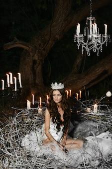 Brunetka modelka z delikatnym makijażem w białej bieliźnie z koroną na głowie siedzi w ogromnym gnieździe na zewnątrz