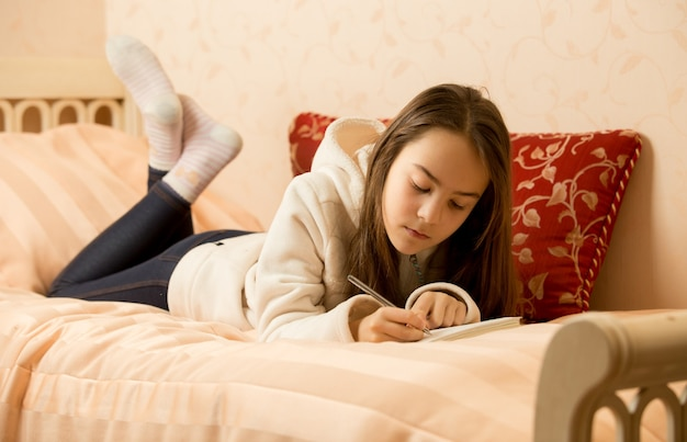 Brunetka nastolatka robi notatki w osobistym pamiętniku
