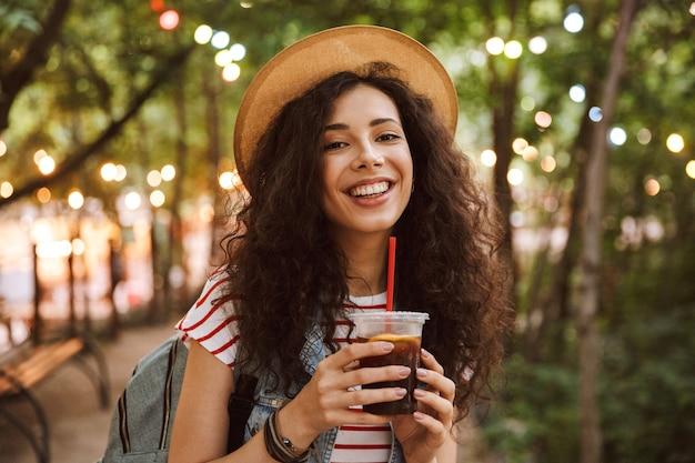 Brunetka nastoletnia kobieta w letnim słomkowym kapeluszu pije zimną herbatę z plastikowego kubka, spacerując po parku z kolorowymi lampami