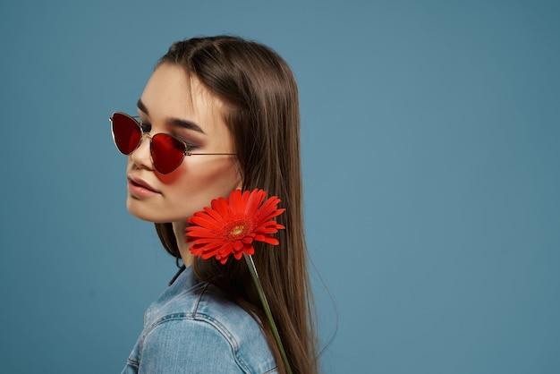Brunetka nosi okulary przeciwsłoneczne czerwony kwiat luksusowy romans niebieskie tło