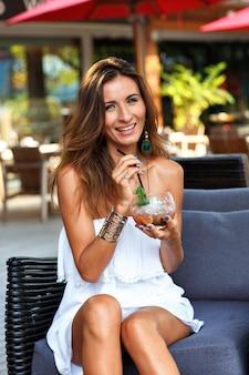 Brunetka opalona piękna kobieta relaksuje się i bawi na tarasie hotelowej restauracji