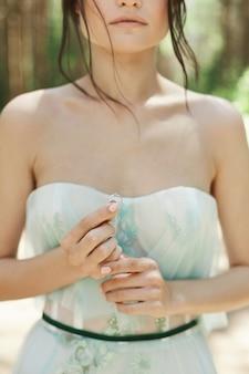 Brunetka panna młoda, trzymając w ręku pierścień ślubny
