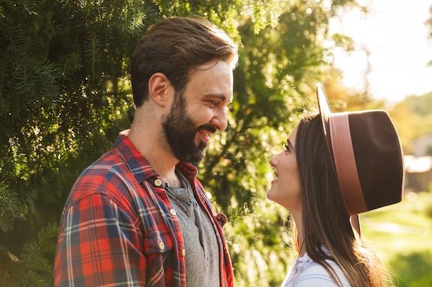 Brunetka para mężczyzna i kobieta ubrani w codzienny strój, uśmiechający się, patrząc na siebie w zielonym parku
