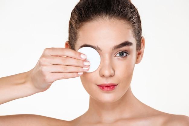 Brunetka piękna kobieta usuwając makijaż oczu z balsamem i wacikiem