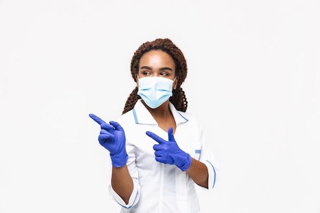 Brunetka pielęgniarka nosząca medyczną maskę na twarz i jednorazowe rękawiczki wskazujące palcami na copyspace odizolowane od białej ściany