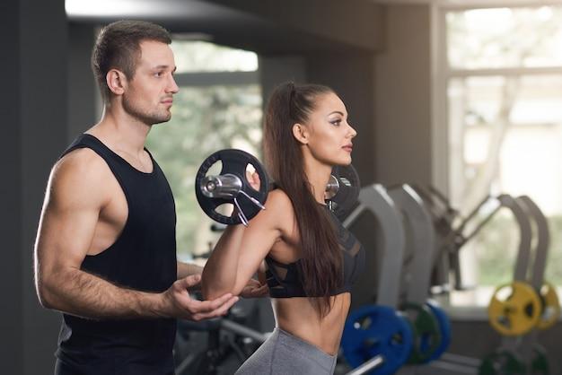 Brunetka podnosi sztangę w siłowni, pomaga trener.