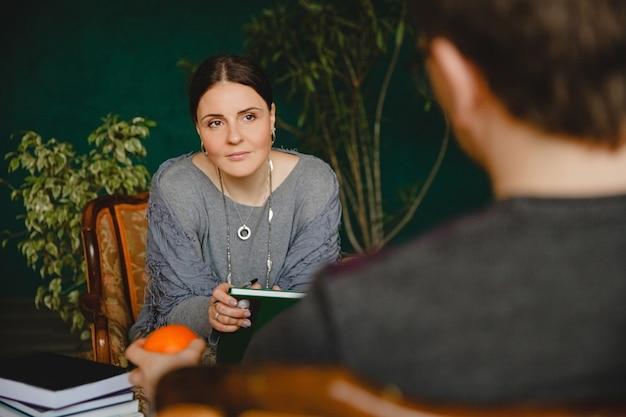 Brunetka psycholog o europejskim wyglądzie przeprowadza wizytę pacjenta w swoim gabinecie