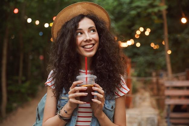 Brunetka radosna nastolatka w słomkowym kapeluszu, pije napój z plastikowego kubka i spaceruje po zielonym parku z kolorowymi lampami