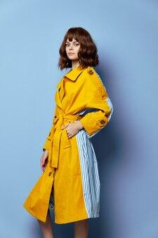 Brunetka ręka w kieszeni żółtego płaszcza z krótkimi włosami jasny makijaż niebieska przestrzeń