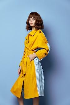 Brunetka ręka w kieszeni żółty płaszcz z krótkimi włosami jasny makijaż niebieskie tło