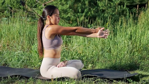 Brunetka robi próżnię z jogi na macie gimnastycznej na tle małych sosen.